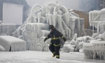 Chicago Fire Department Lieutenant De Jesus walks around an ice-covered warehouse that caught fire Tuesday night in Chicago